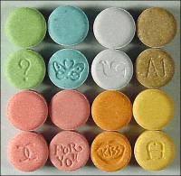 Foto-Abbildung von Ecstasy-Tabletten in verschiedenen Farben und mit verschiedenen eingepressten Symbolen, wie beispielsweise Schmetterlinge und Vögel.